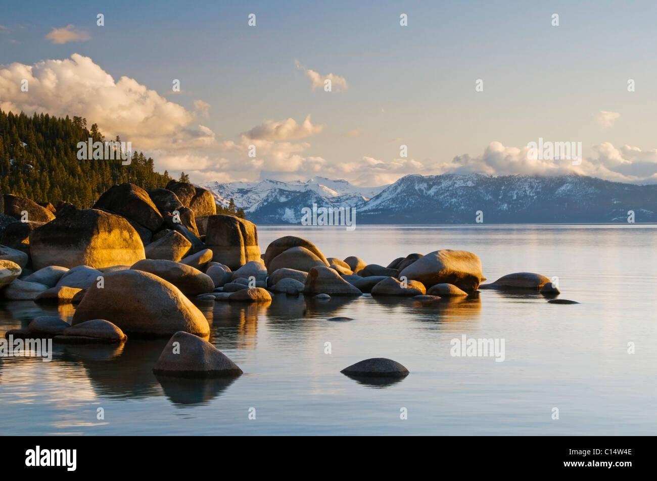 Golden afternoon light illuminates granite boulders on the east shore of Lake Tahoe, NV. - Stock Image