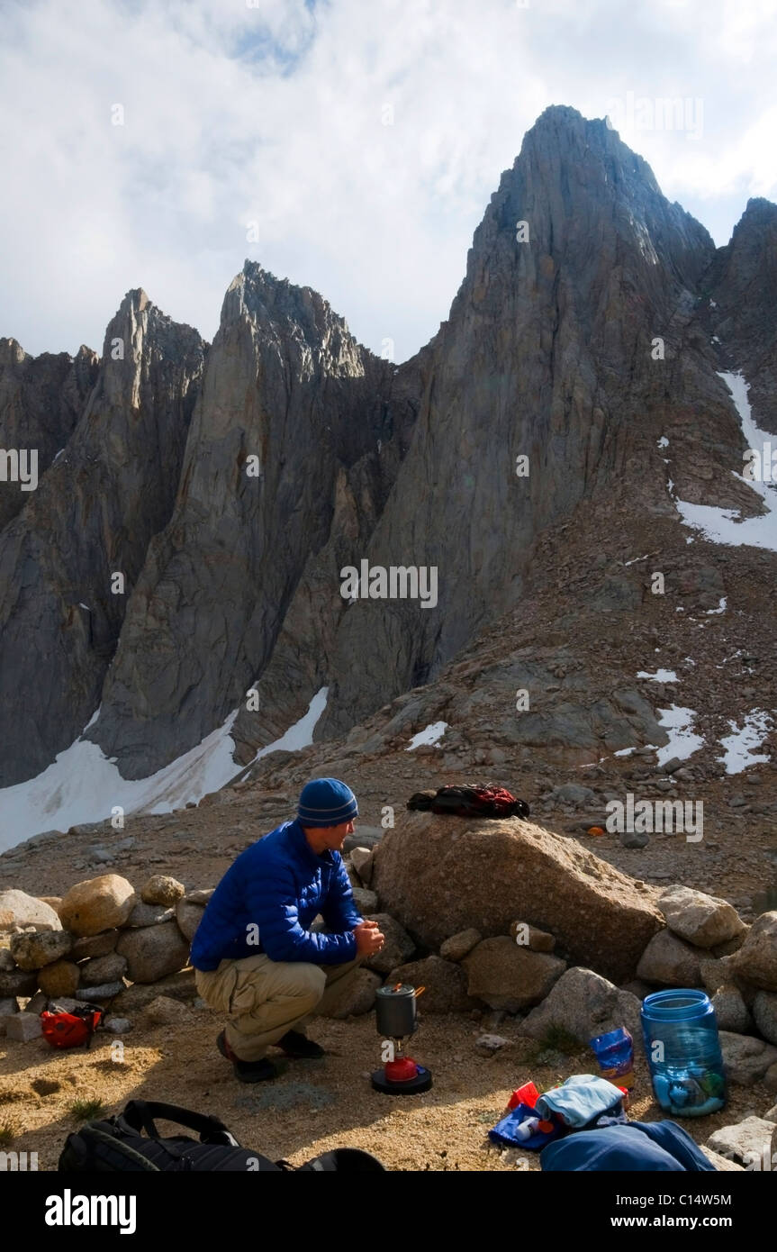 A man boils some water at camp below Mount Whitney in the Eastern Sierra, CA. - Stock Image