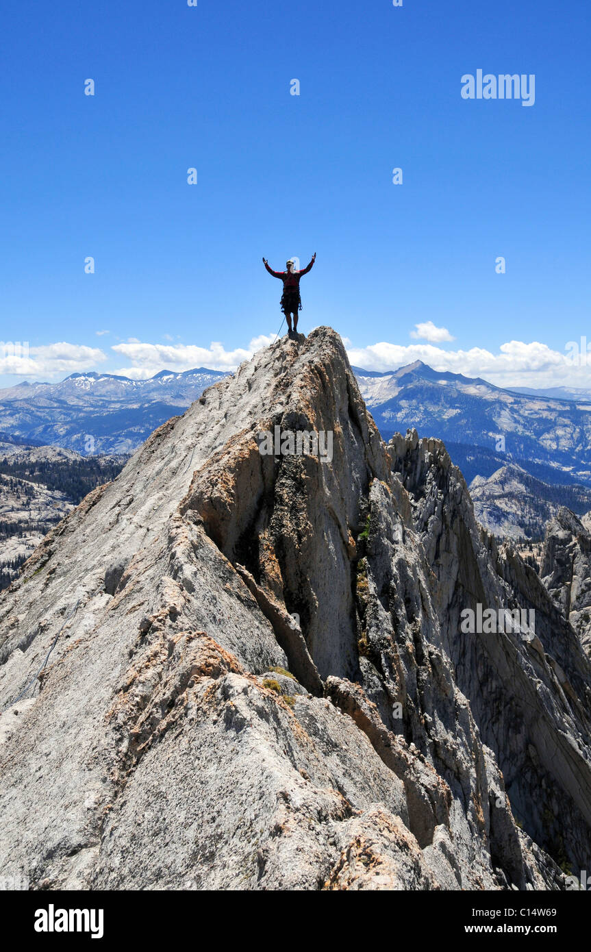A rock climber stands with arms outstretched on Matthes Crest in Yosemite National Park, California. - Stock Image