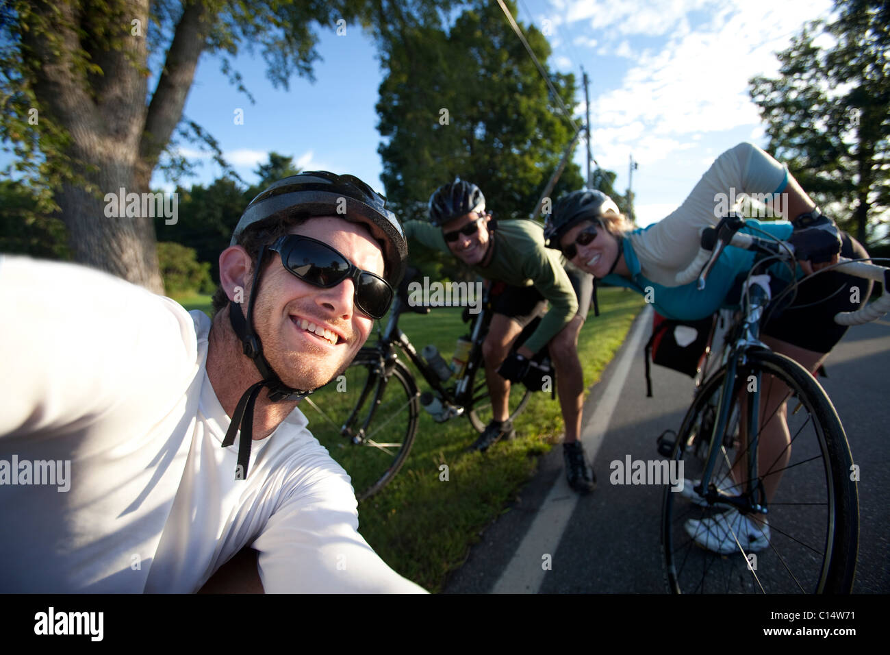Three cyclists smile for a portrait during a bike ride in Monmouth, Maine. - Stock Image