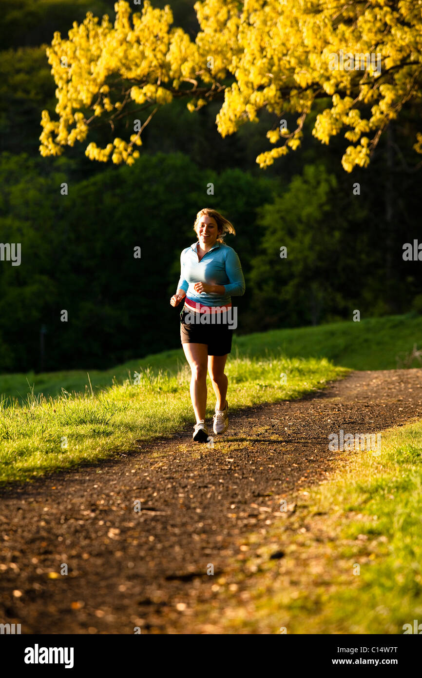 A woman smiles while running along a trail in Rockefeller State Park in Sleepy Hollow, New York. - Stock Image
