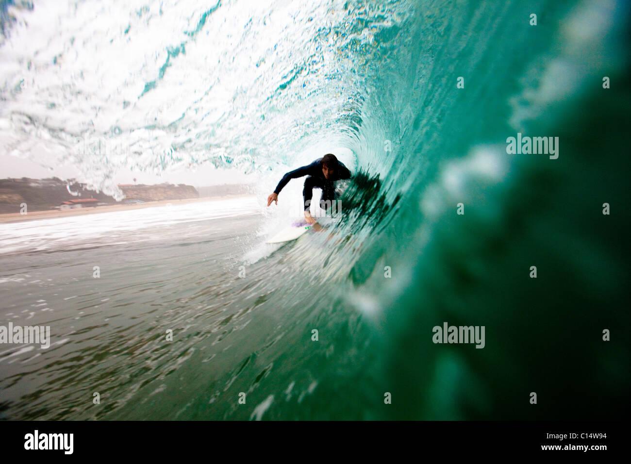 A male surfer pulls into a barrel while surfing at Zuma beach in Malibu, California. - Stock Image