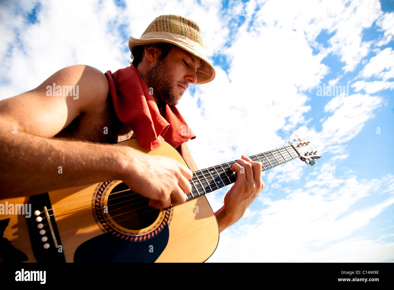 A young man plays his guitar while on a fishing boat off the coast of Malakati, Fiji. - Stock Image