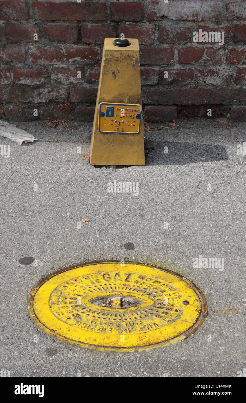 Yellow gas network marker and pavement access cover in Morbecque, Nord-Pas-de-Calais, France. - Stock Image