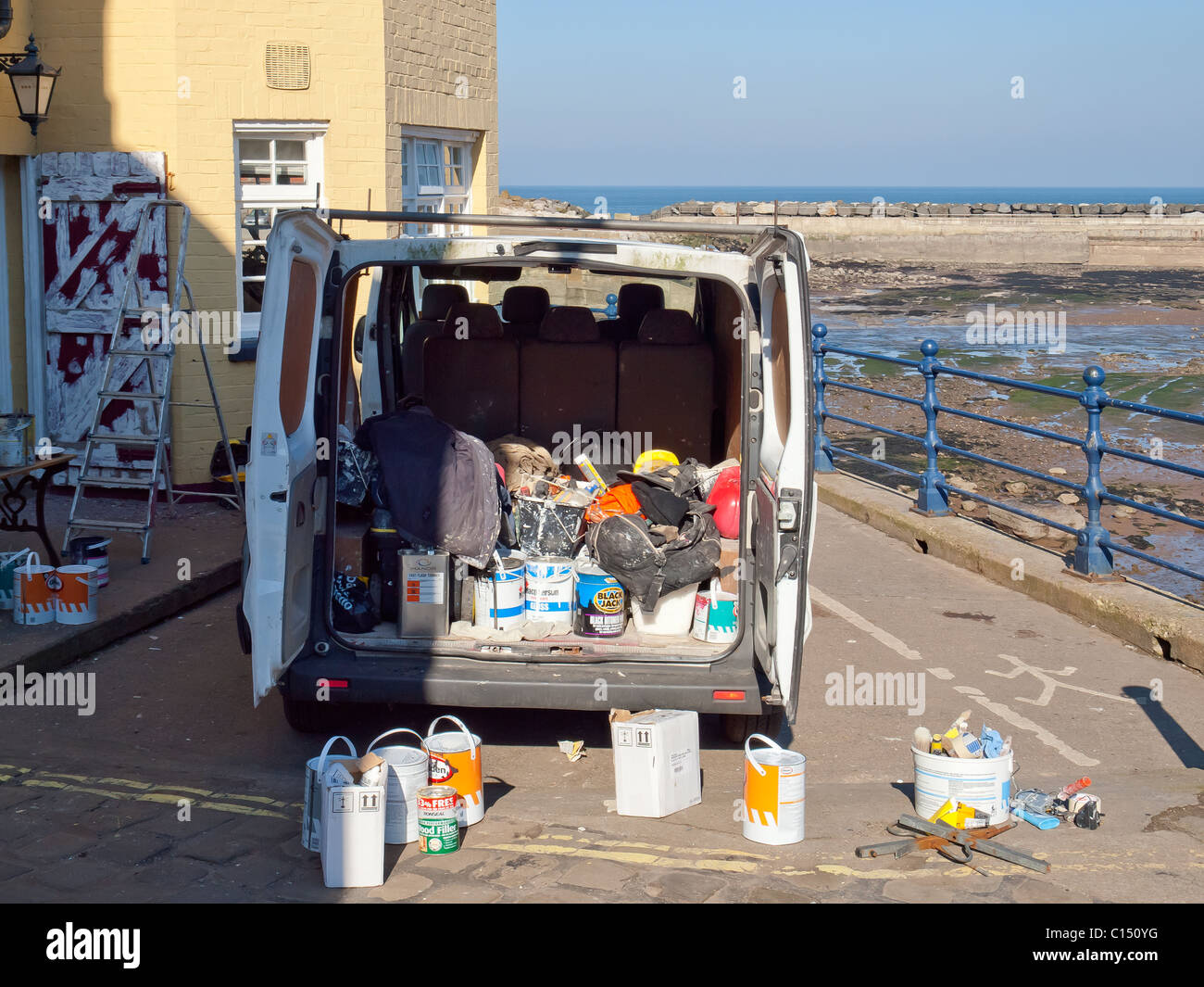Painter and decorator's van with rear doors open and many paint tins exterior decoration of a seaside pub - Stock Image