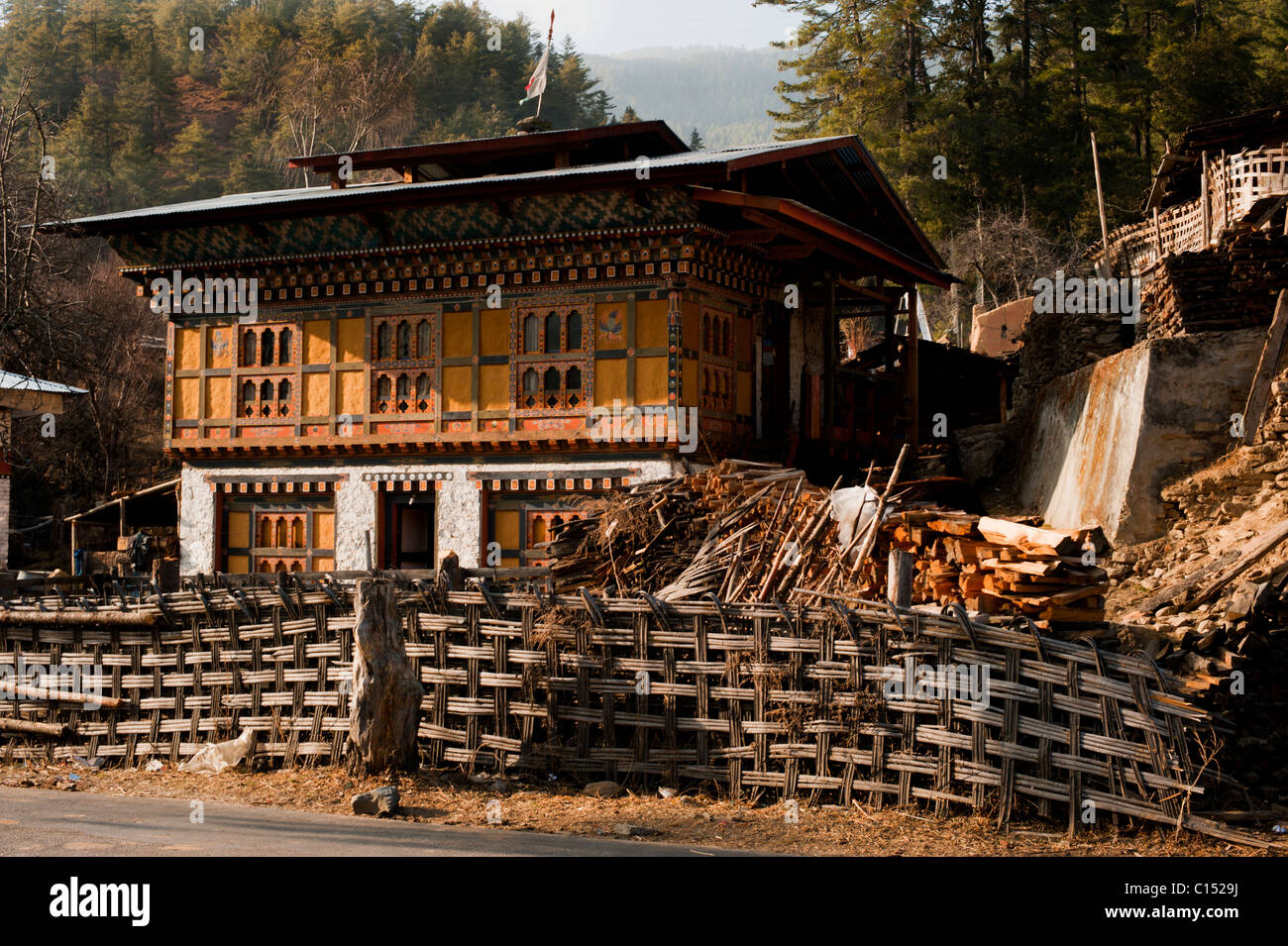 Traditional Bhutanese house in rural Bhutan with wooden details and traditonal bamboo fence. - Stock Image
