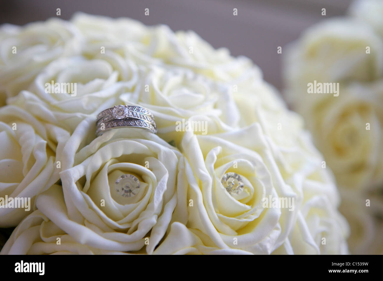 Diamond engagement ring in a wedding flower bouquet of white roses ...