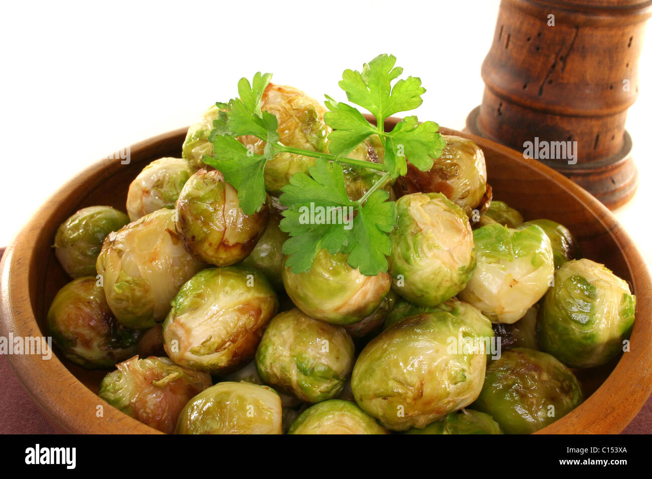 roasted brussels sprouts in a wooden bowl on a brown napkin Stock Photo