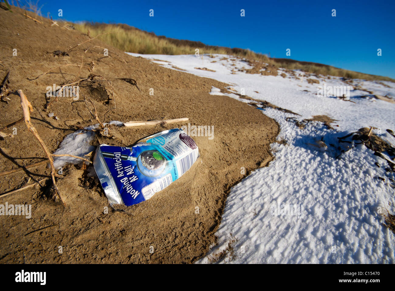 A plastic drinks package saying nothing artificial at all lies in the sand on the beach - Stock Image