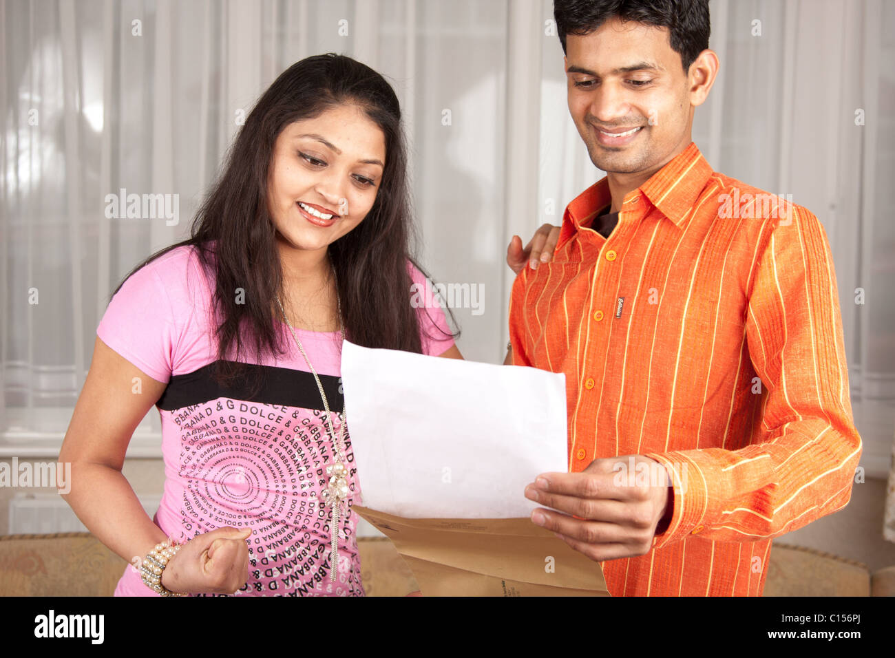 Two colleagues reading the contents of the letter and showing their anxiety by action and smile on their face. - Stock Image