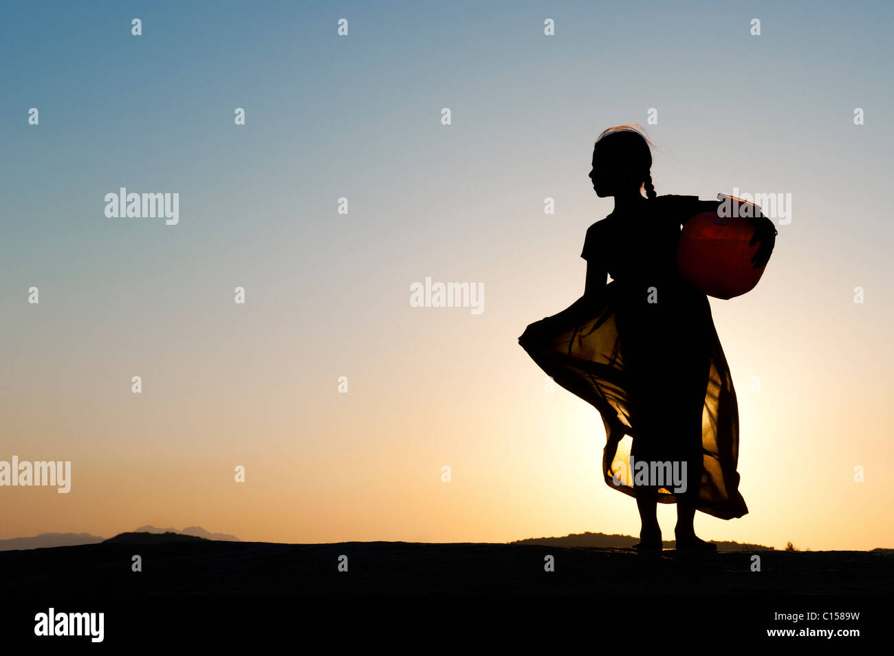 Rural Indian village girl carrying a water pot at sunset. Silhouette. Andhra Pradesh, India - Stock Image