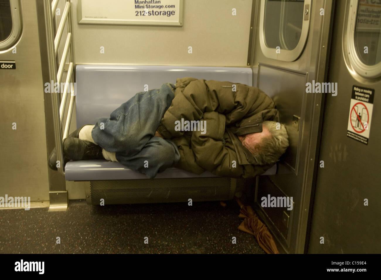 Homeless man sleeping on a New York City subway train - Stock Image