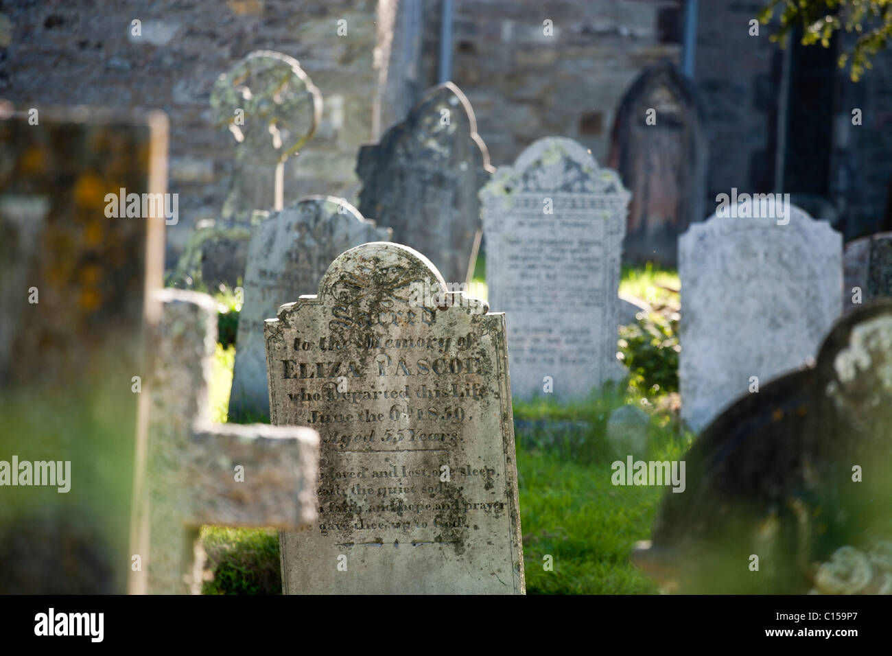 Old Mylor Graveyard. Stones scattered through the old graveyard at Mylor. Mylor, Cornwall, United Kingdom - Stock Image