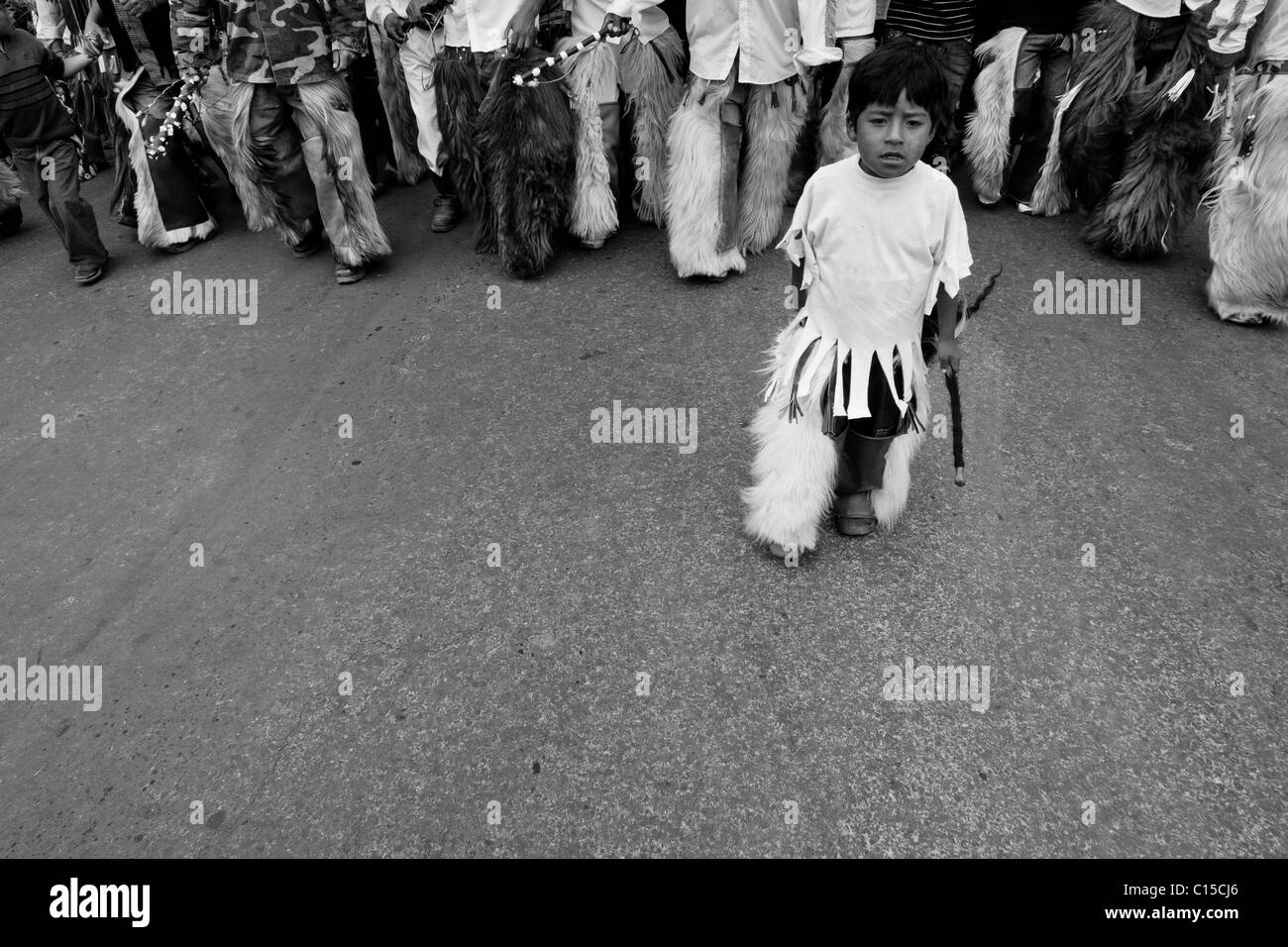 An Indian boy walks at the head of the dancing group during the Inti Raymi (San Juan) festivities in Cotacachi, - Stock Image