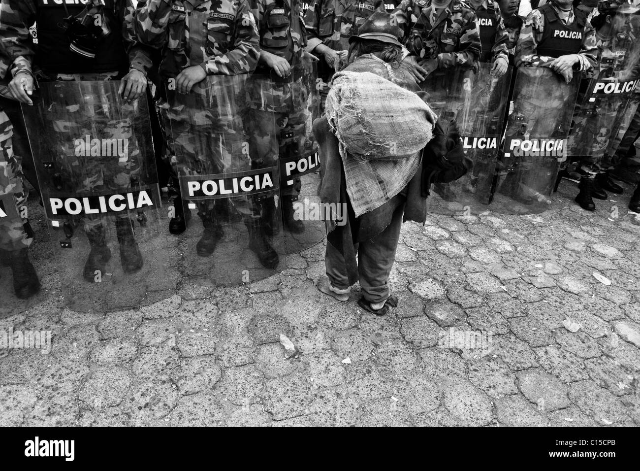An old barefoot Indian passes through the riot police block during the Inti Raymi (San Juan) festivities in Cotacachi, - Stock Image