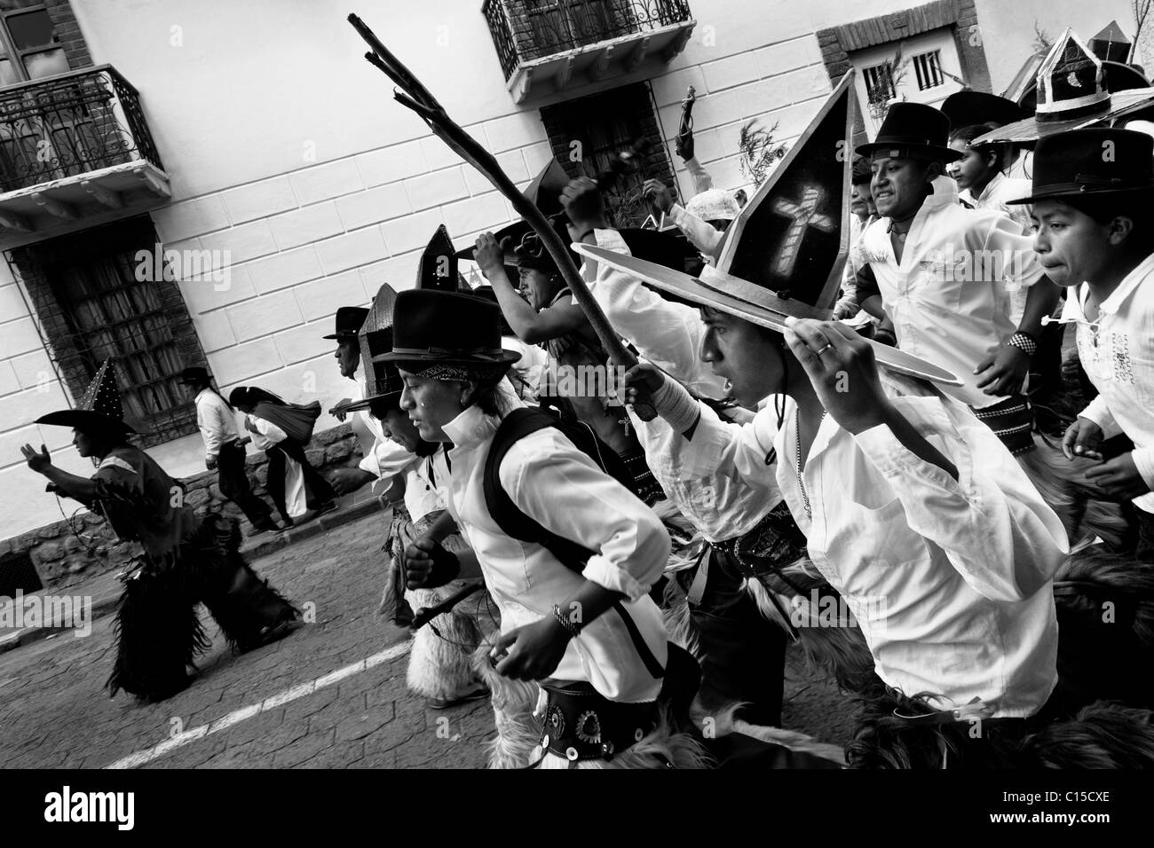 Indians, wearing white shirts, dance and shout furiously during the Inti Raymi (San Juan) festivities in Cotacachi, Stock Photo
