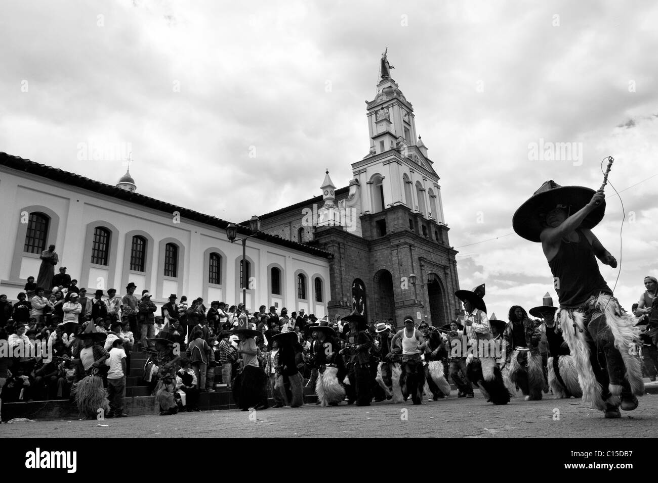 Indians, wearing goatskin chaps, dance furiously during the Inti Raymi (San Juan) festivities in front of the church Stock Photo