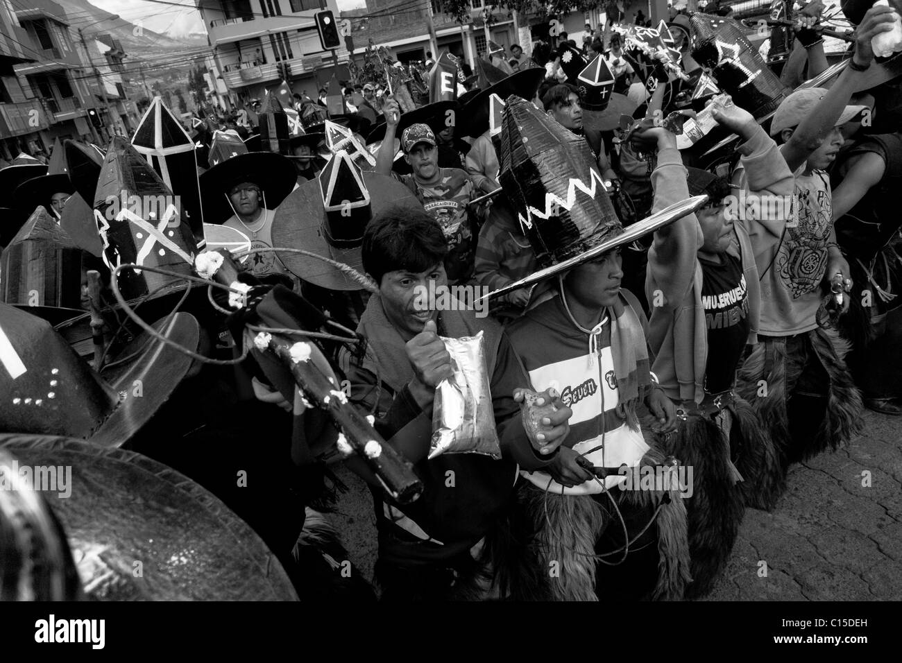 Indians, wearing black cardboard hats, dance and shout furiously during the Inti Raymi  festivities in Cotacachi, - Stock Image