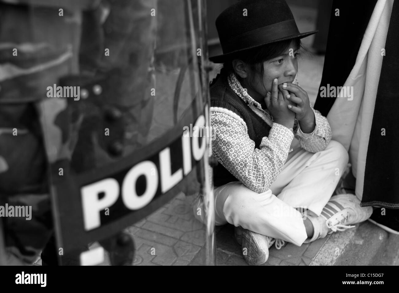 An Indian boy sits on the pavement next to a riot policeman during the Inti Raymi (San Juan) festivities in Cotacachi, - Stock Image