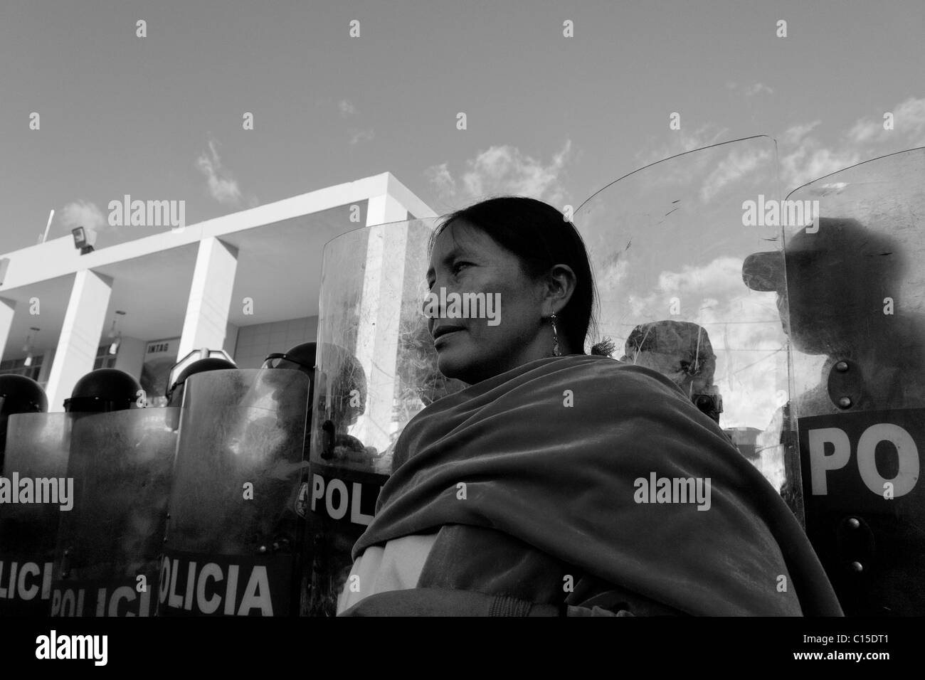 An Indian woman stands in front of the riot police block during the Inti Raymi (San Juan) festivities in Cotacachi, - Stock Image