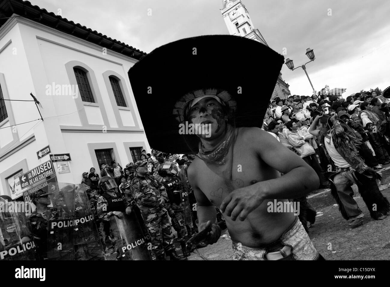 An Indian, wearing a large cardboard hat, dances in front of the police block during the Inti Raymi festivities - Stock Image