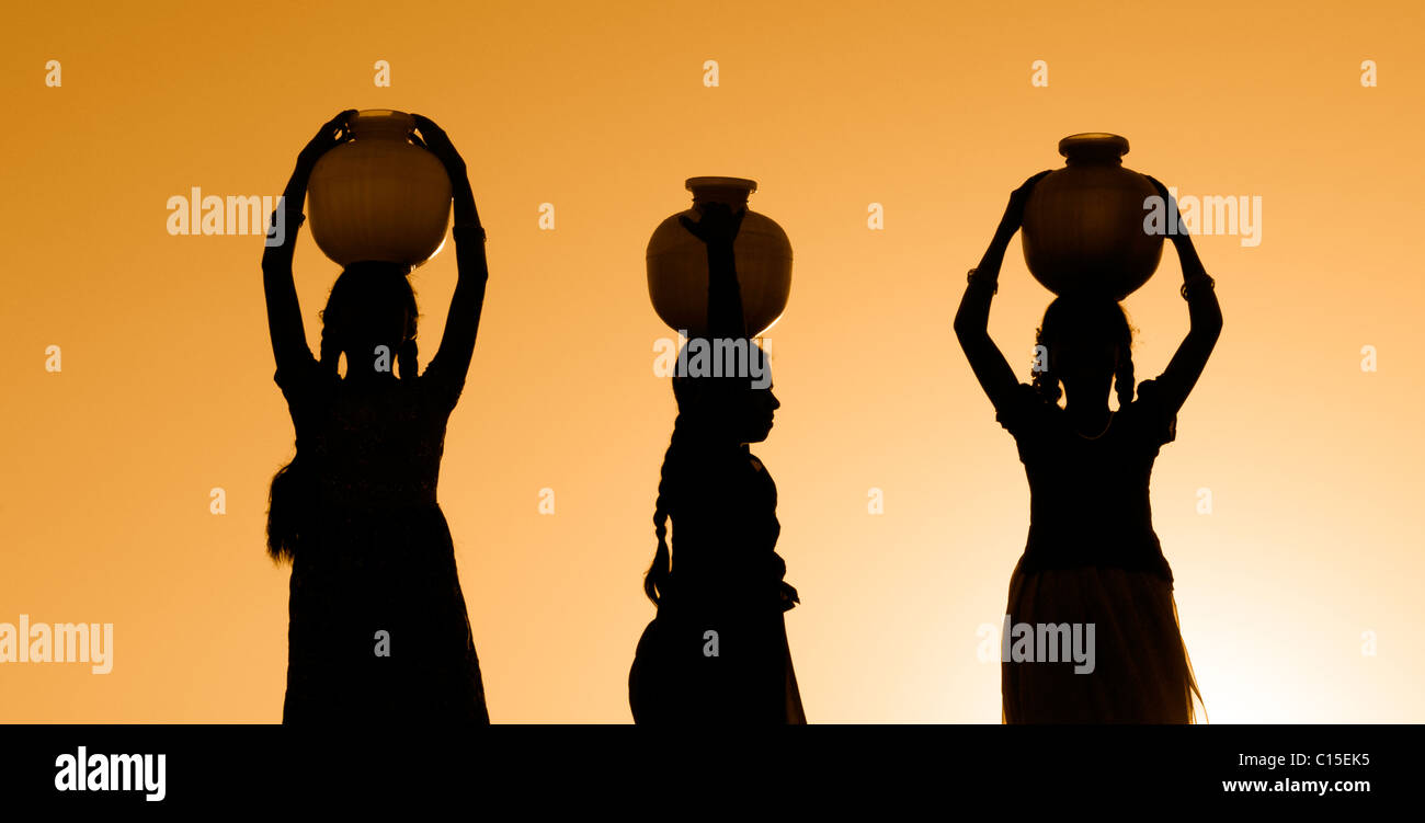 Rural Indian village girls balancing a water pot on their heads at sunset. Silhouette. Andhra Pradesh, India - Stock Image