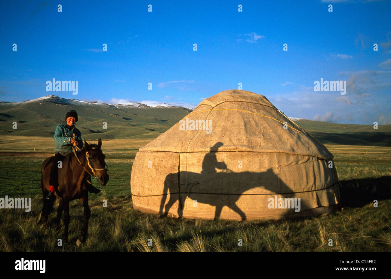 Horse and rider in front of a yurt, Moldo-Too Mountain Range, Song-Kul, Kyrgyzstan, Central Asia Stock Photo