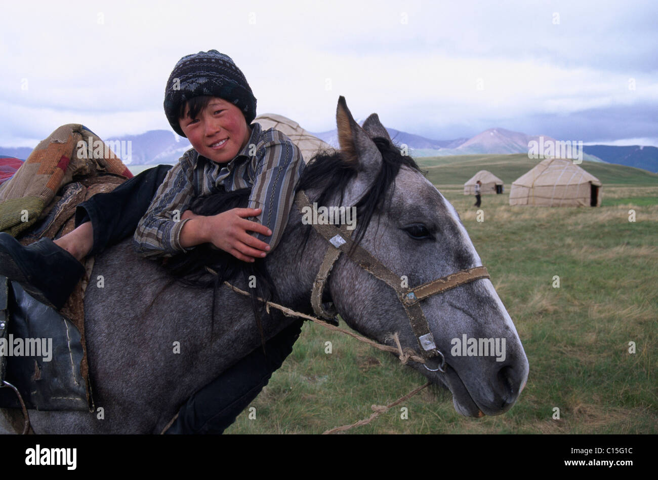 Boy and horse at Lake Song Kul, Kyrgyzstan, Central Asia - Stock Image
