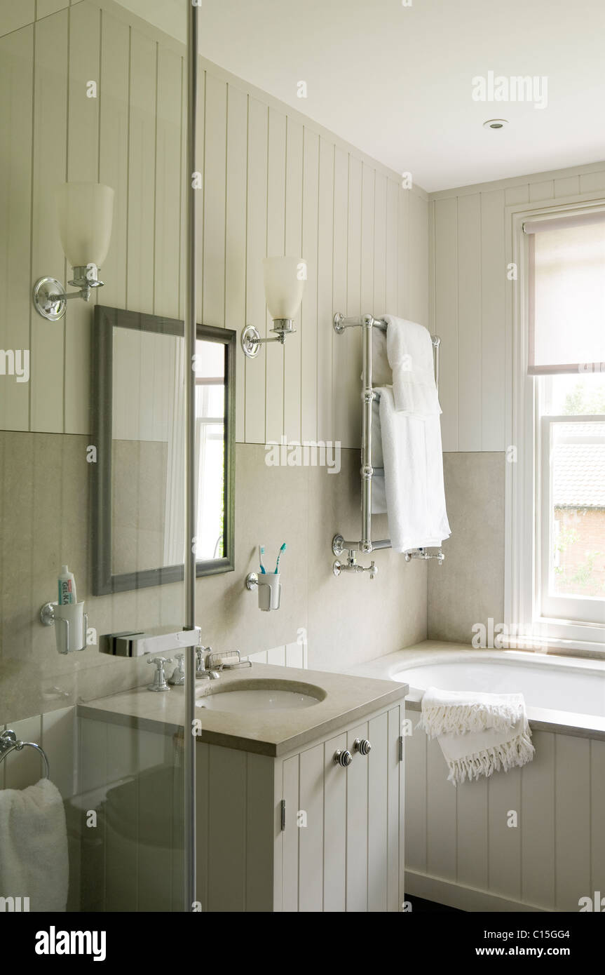 All white bathroom with wooden panelling and wall sconce lamps Stock ...