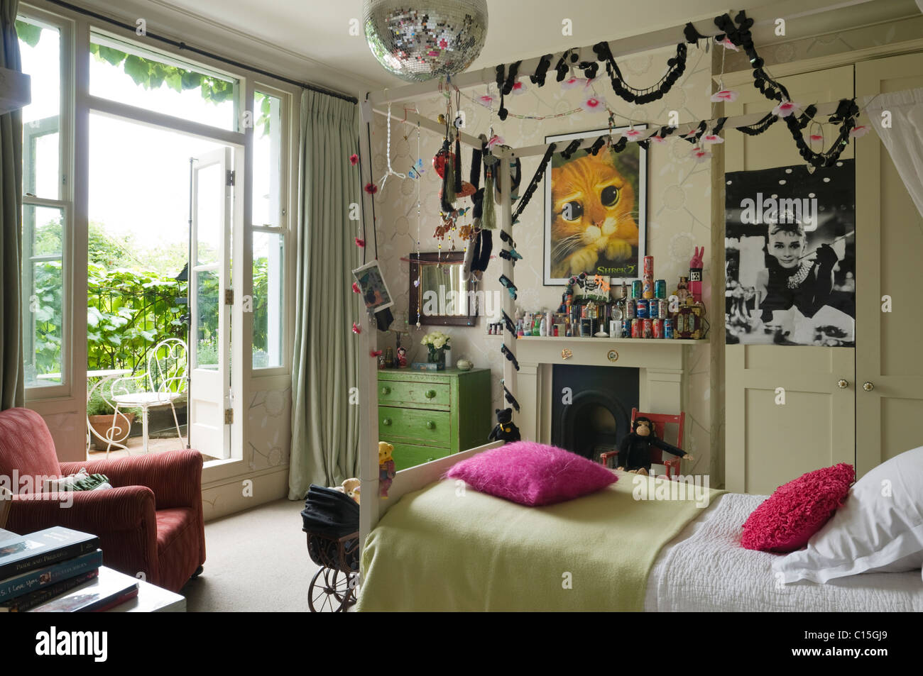 Single four poster bed in teenage girl's bedroom - Stock Image