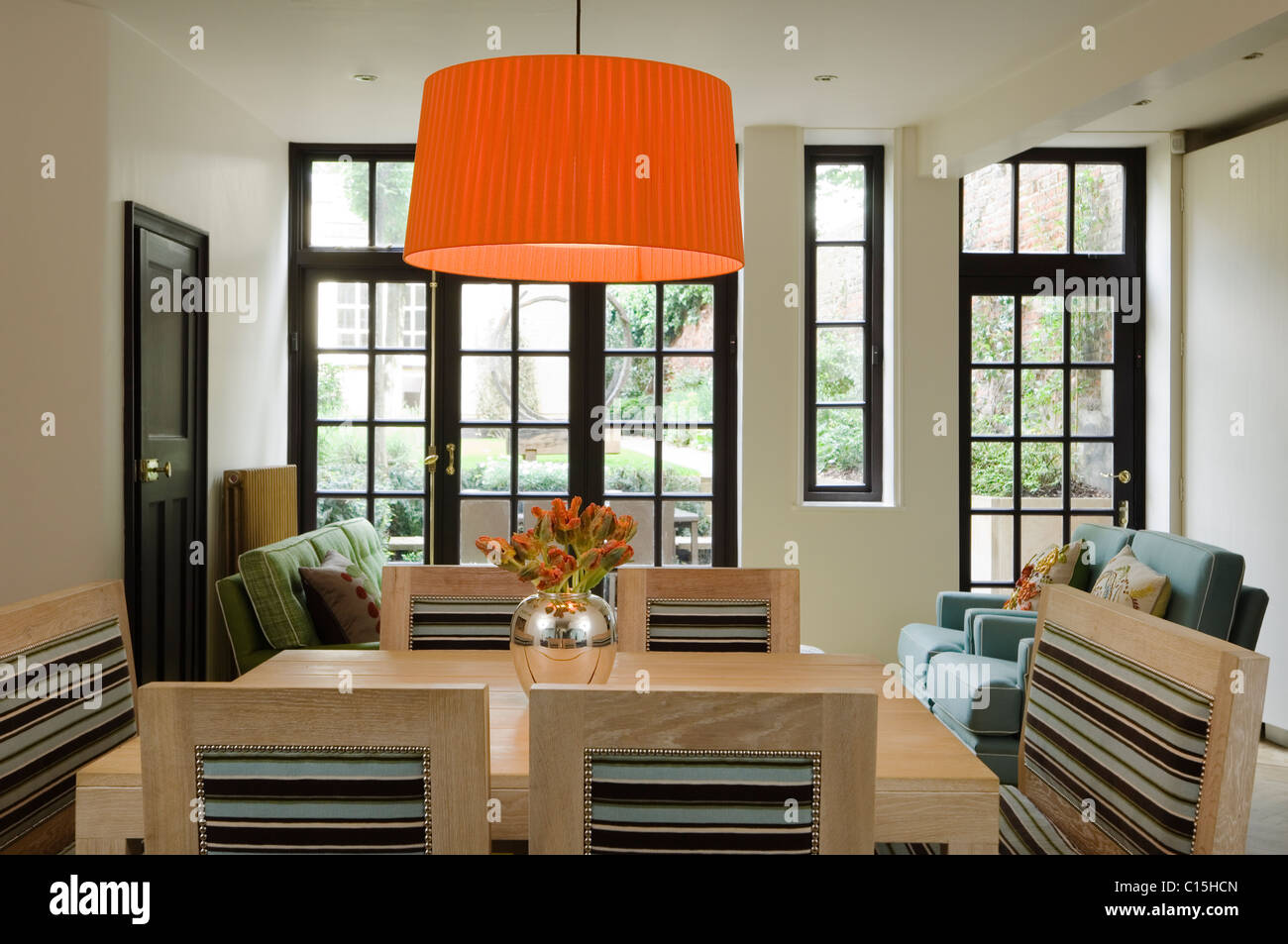 Large orange lampshade above wooden dining table in room with glass large orange lampshade above wooden dining table in room with glass panelled windows aloadofball