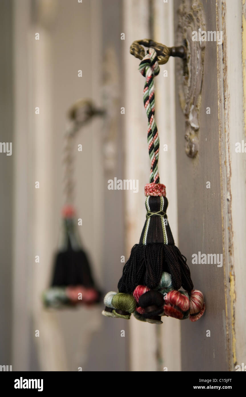 A tassel tied to an old fashioned key in the lock of a french cupboard - Stock Image