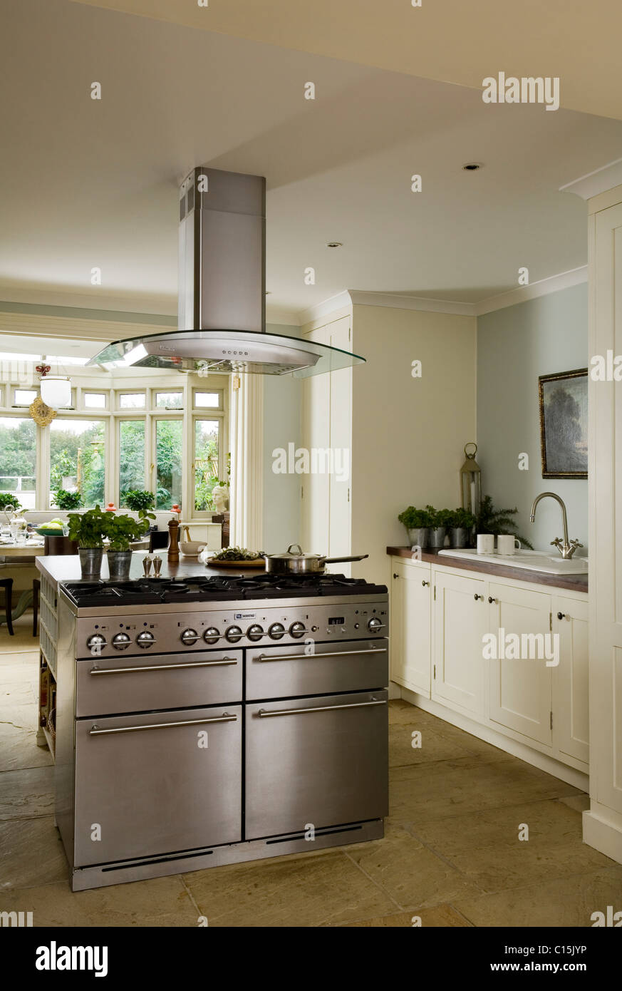 Modern white kitchen with stainless steel island hob and extractor ...