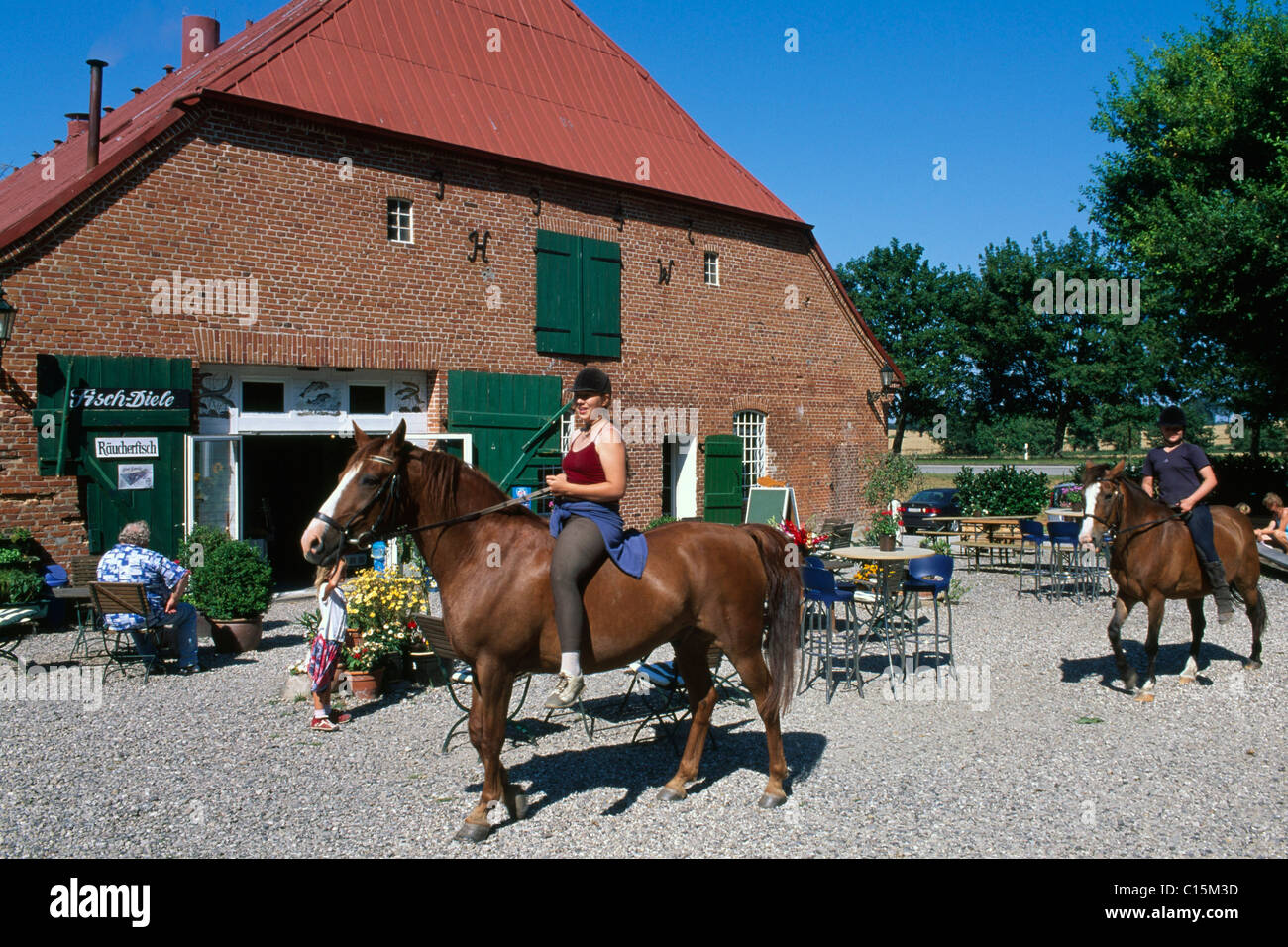 Horse riders in front of the Bauernhof-Cafe, Farm Cafe of Gut Goertz, Schleswig-Holstein, Germany, Europe - Stock Image