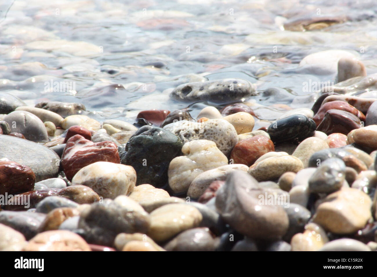Sunlit wet pebbles on the beach with the tide gently lapping over them. - Stock Image