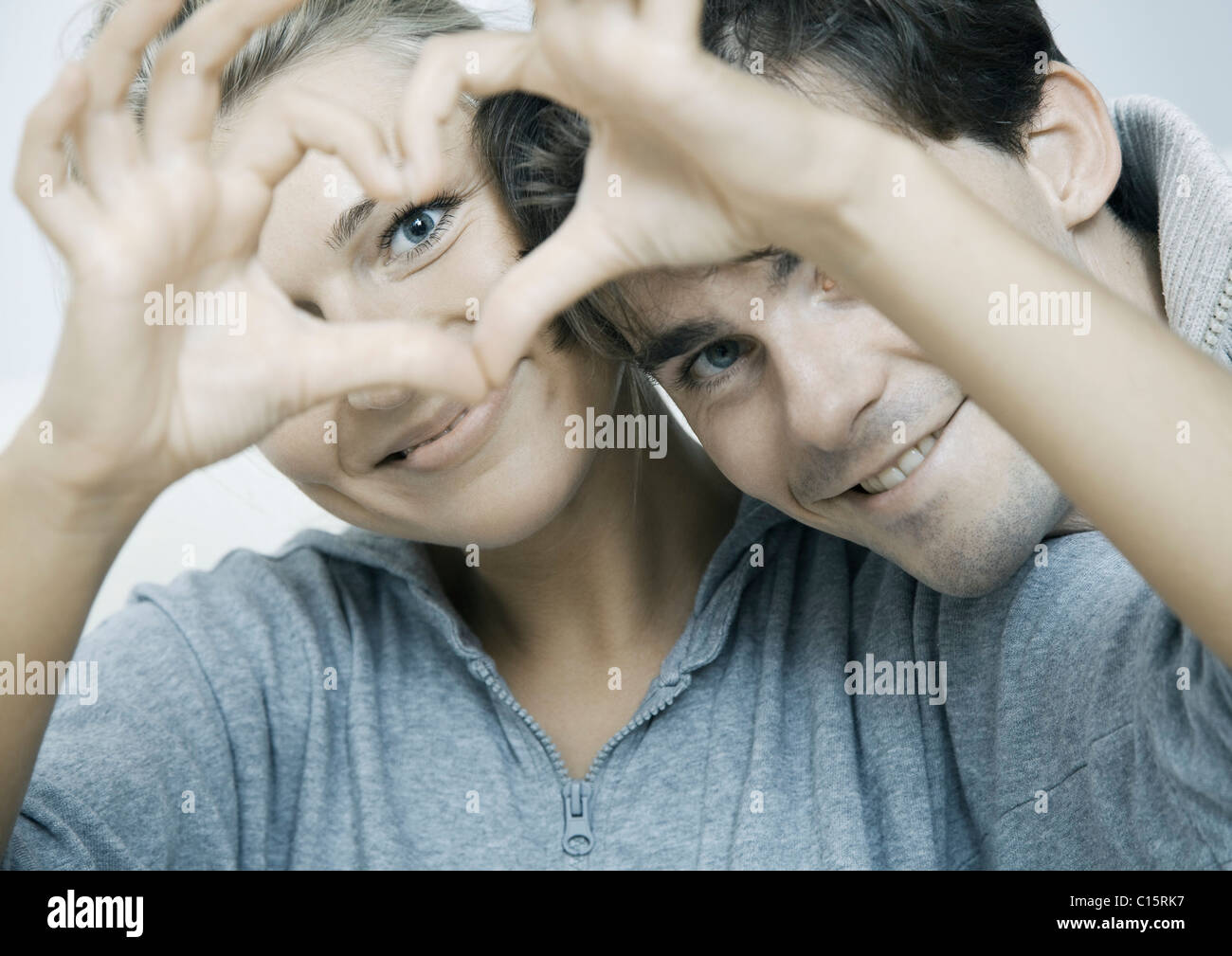 Young couple in love making heart their hands