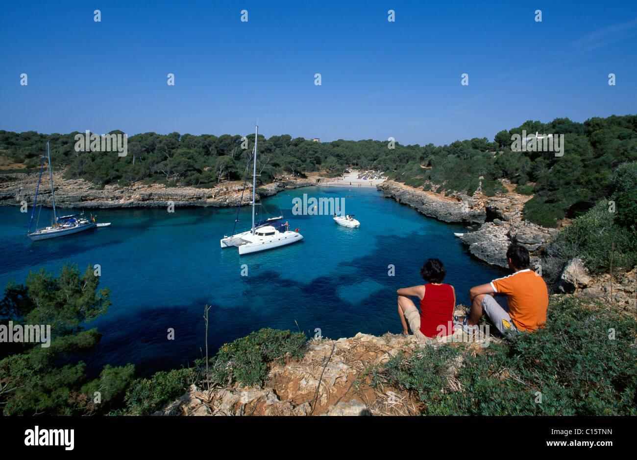 Couple sitting on rocks in the Cala Sa Nau Bay, Balearic Islands, Europe - Stock Image