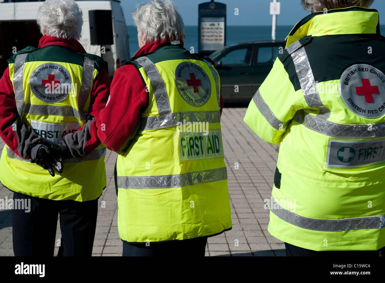 Rear view of three British Red Cross first aid volunteers, UK - Stock Image