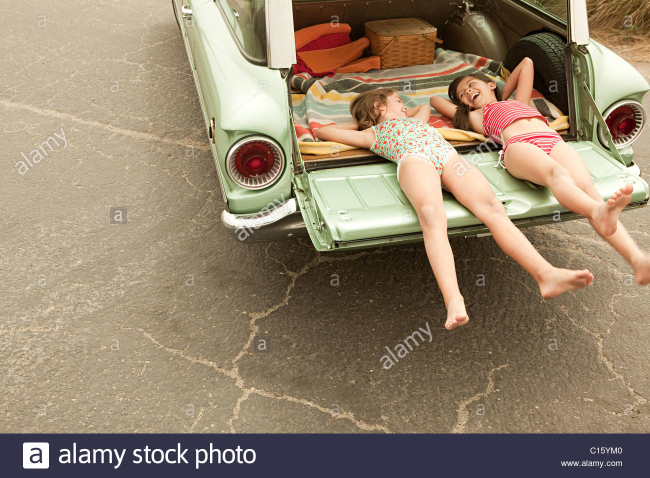 Two girls lying in estate car - Stock Image