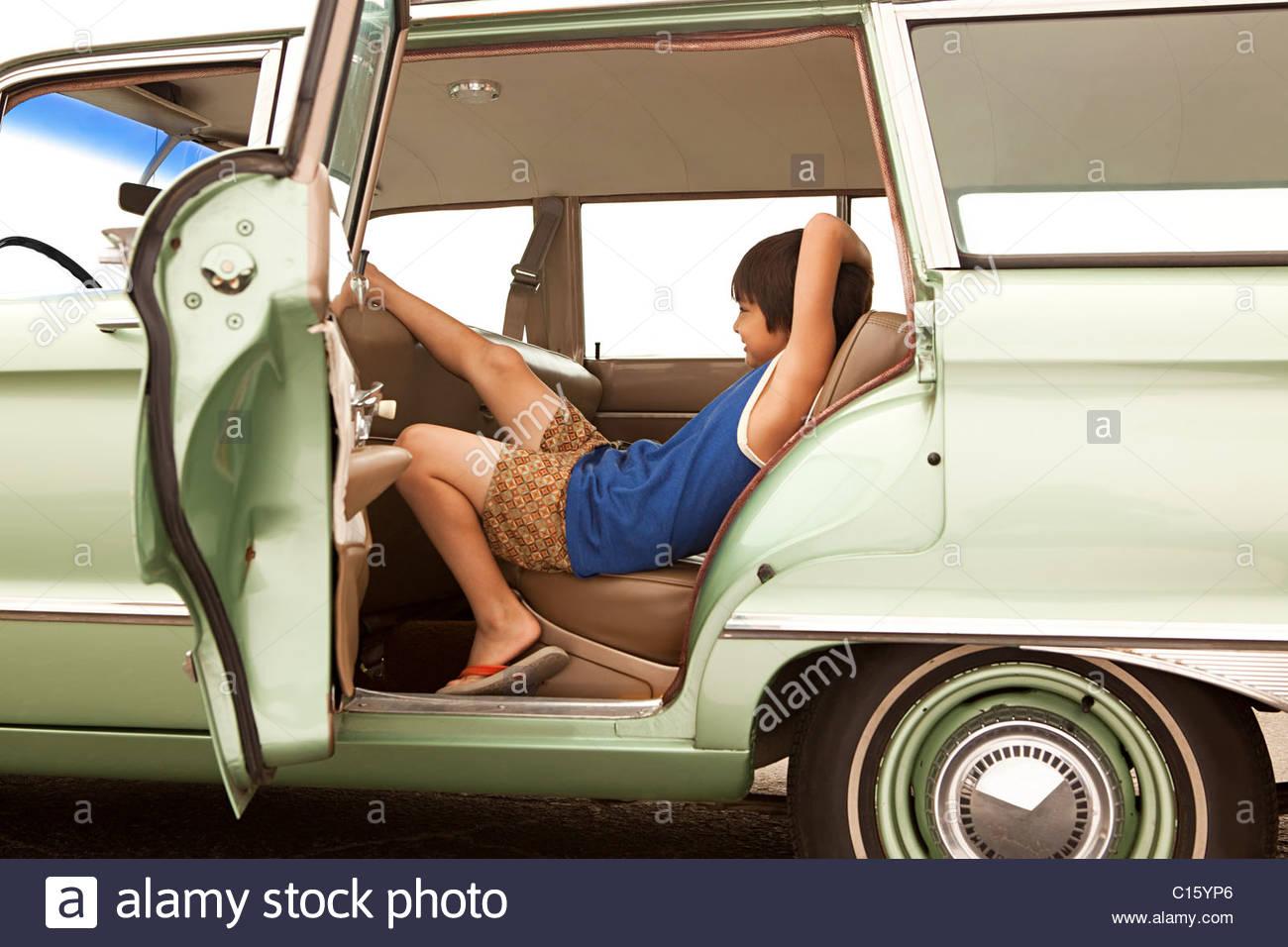 Sullen boy sitting in car - Stock Image