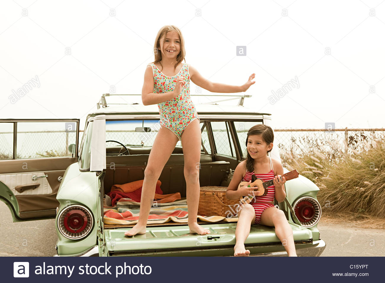 Girl dancing on car boot, another girl playing guitar - Stock Image