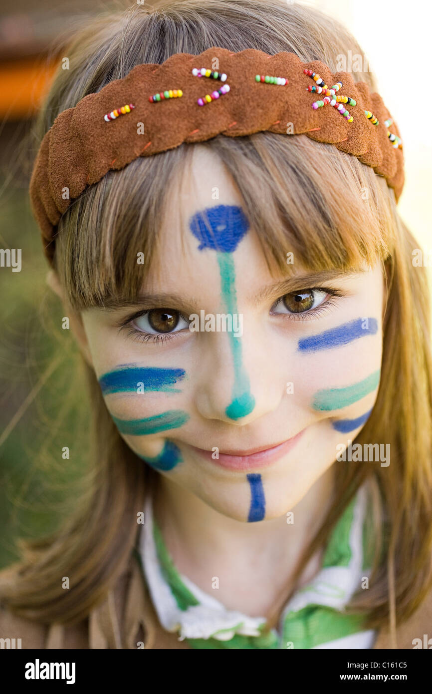Girl dressed in Native American costume with face painted - Stock Image