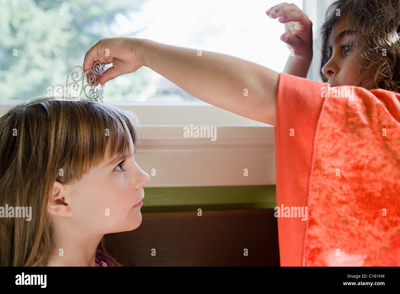 One girl putting tiara on another girl - Stock Image