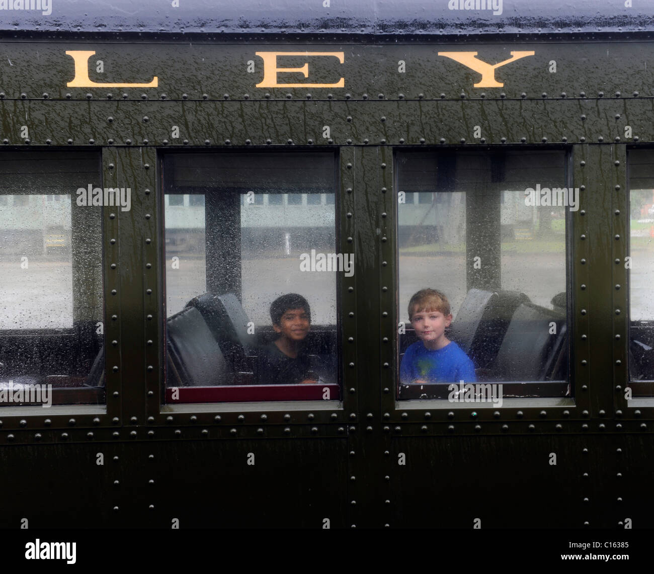 7 year old boys ride the historic Essex Steam Train on a rainy day - Stock Image