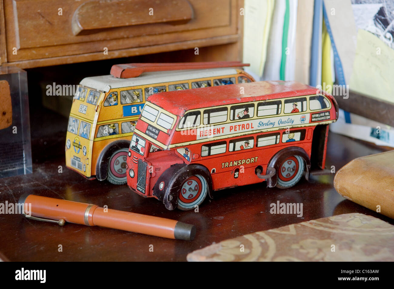 Pair of vintage London bus toys on desk top with pen. - Stock Image