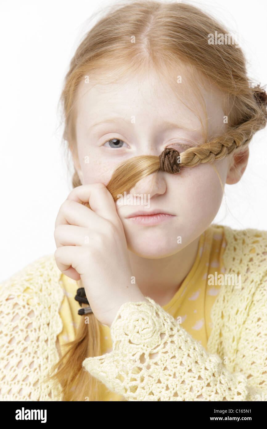 Girl, 8 years old, holding a braid in front of one of her eyes Stock Photo