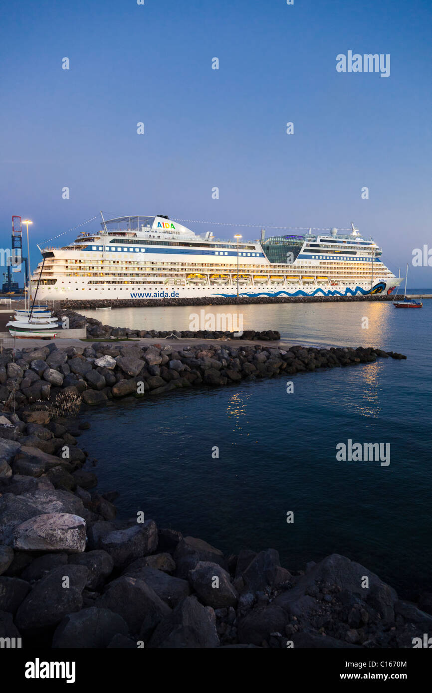 The luxury cruise liner AIDAblu at dusk leaving the harbour of Puerto del Rosario on the Canary Island of Fuerteventura - Stock Image