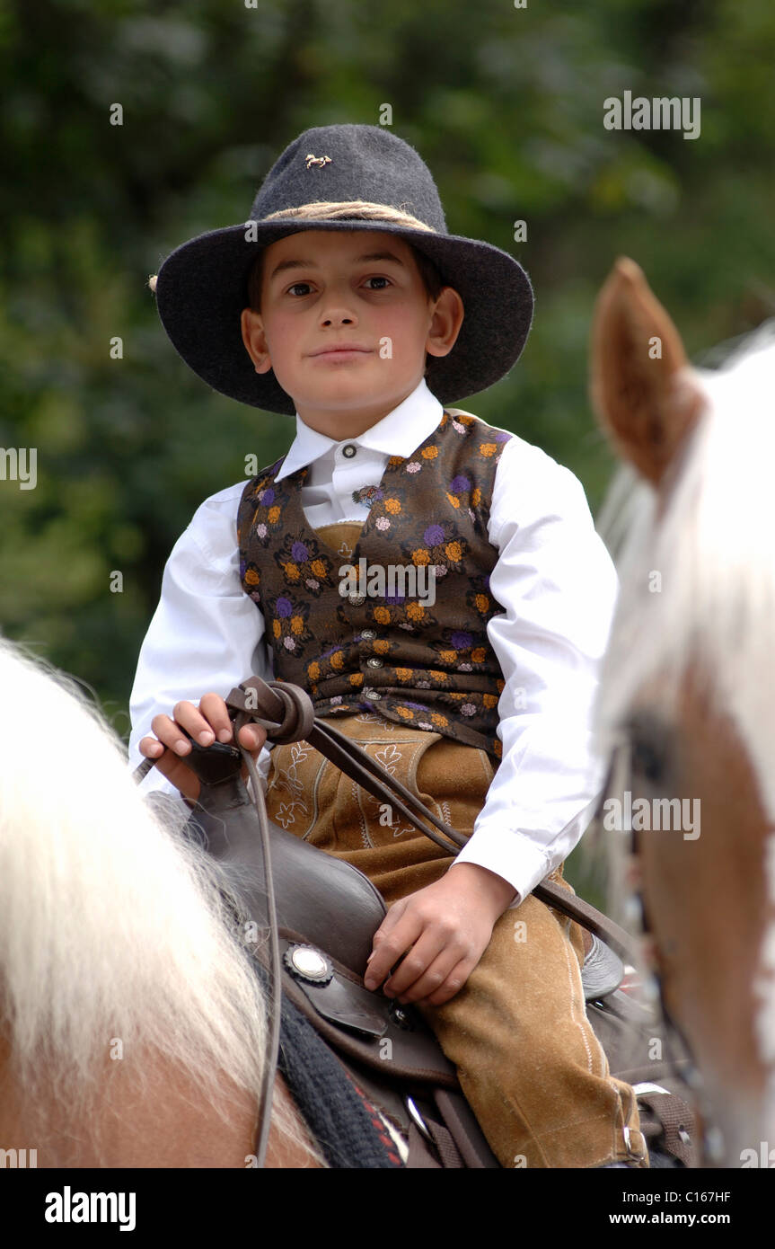 Young boy horseman riding a Haflinger horse during a traditional procession in the village of Santa Cristina in Stock Photo
