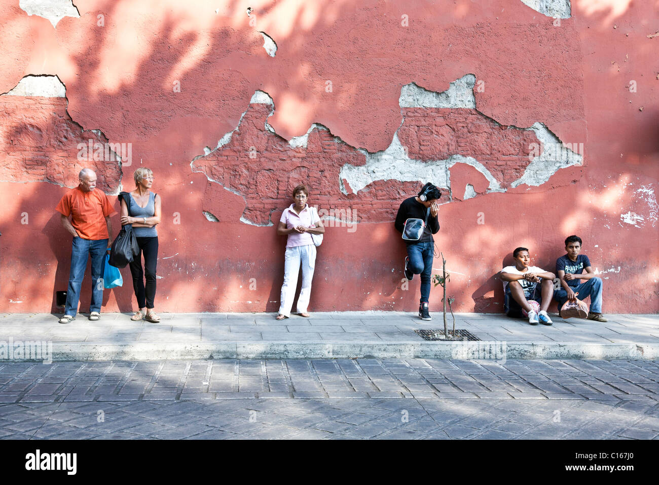 diverse group of people wait at bus stop against marvelous old crumbling red plaster wall in Oaxaca Mexico - Stock Image