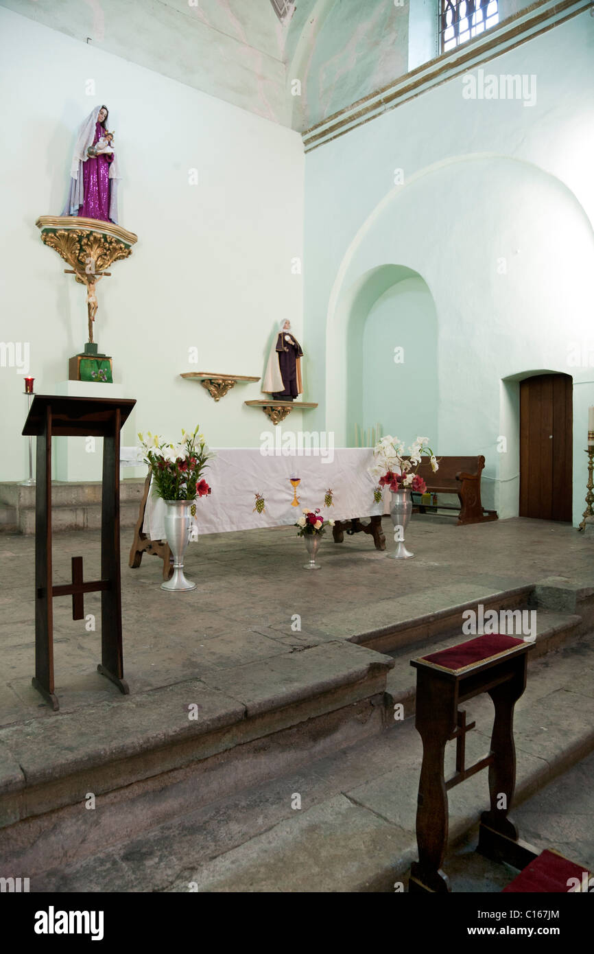 elegantly simple wooden prie dieu in front of priests lectern next to altar with fresh flowers in sanctuary of old - Stock Image